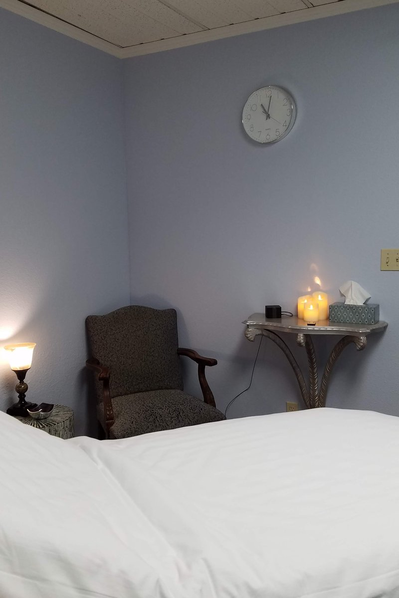 Shared workspace massage room with treatment table and client seating