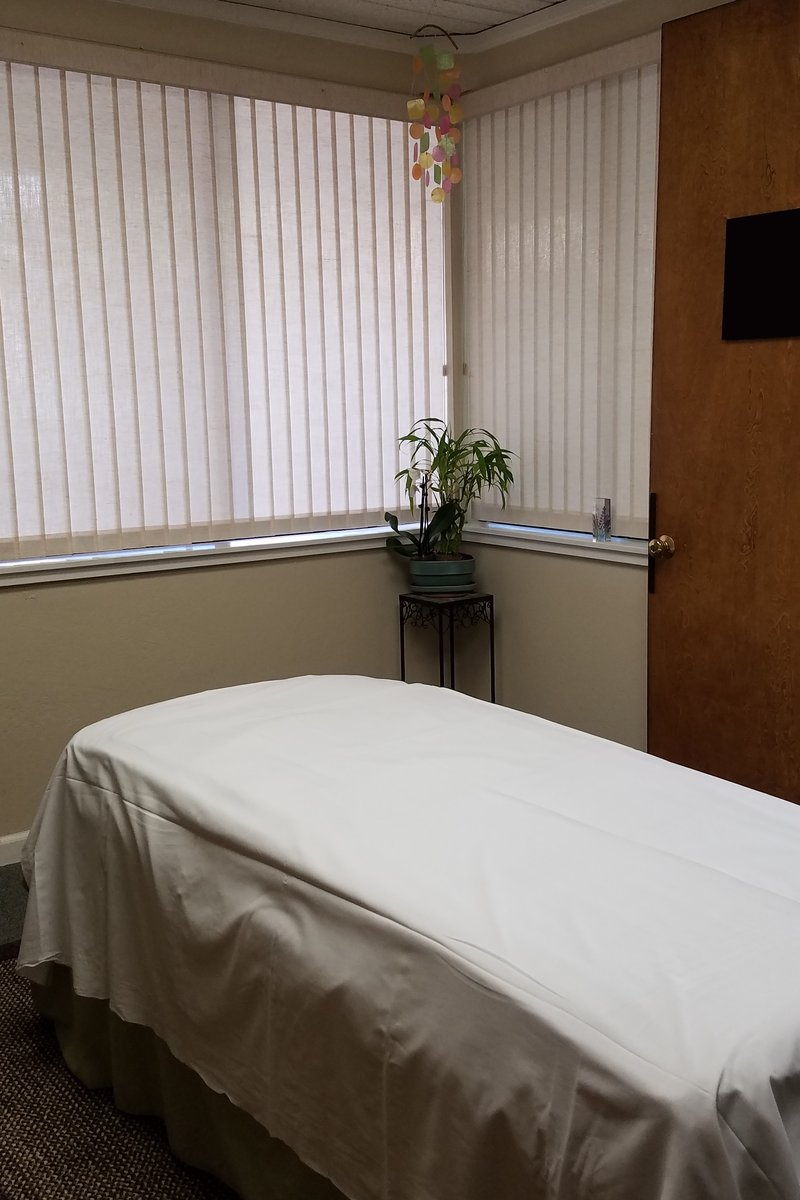 Massage treatment room looking over table toward windows and potted plant